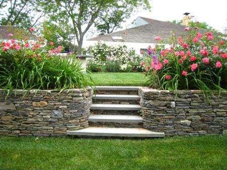 Дві кам'яні клумби з квітами обрамляють садові сходи