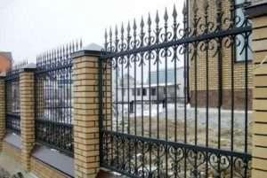 Цегляний паркан з кованими елементами
